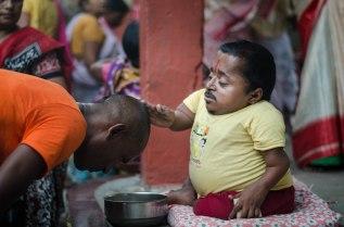 Little man blessing devotees.